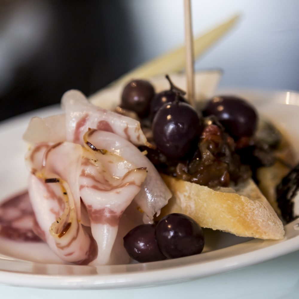 Typical Italian appetizer plate with Sicilian Caponata, bread, cheese, olives, and guanciale.